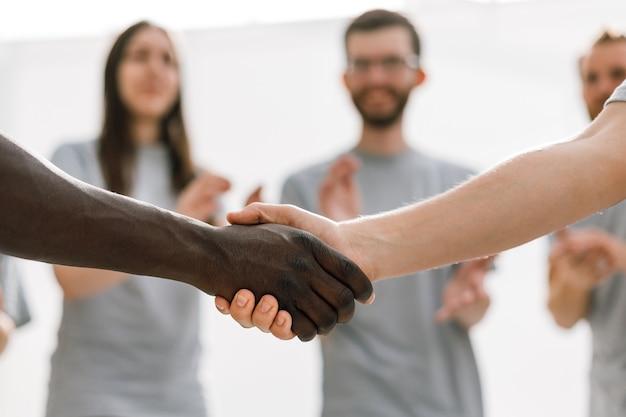 Fechar-se. forte aperto de mão de dois alunos de diferentes nacionalidades. foto com espaço de cópia
