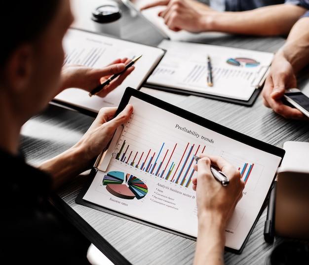 Fechar-se. funcionários discutindo documentos financeiros no local de trabalho. conceito de negócios.