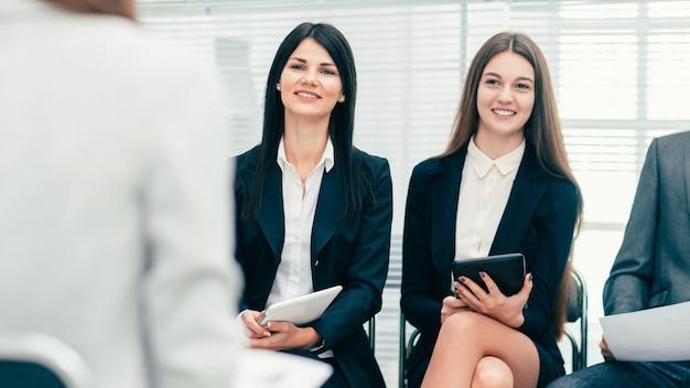 Fechar-se. funcionários fazendo perguntas em uma reunião de trabalho. conceito de negócios