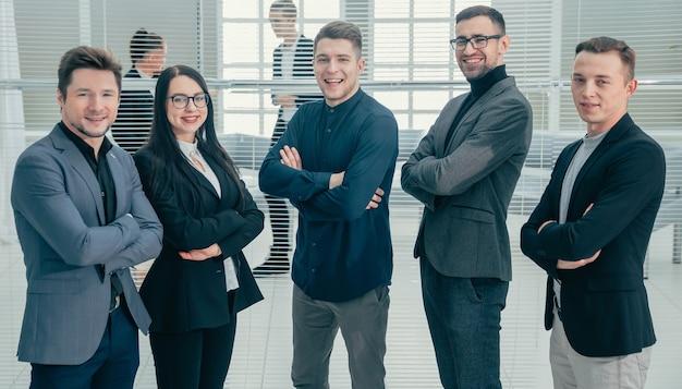 Fechar-se. grupo de jovens profissionais em pé no escritório. conceito de negócios.