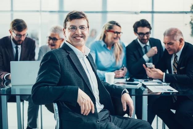 Fechar-se. homem de negócios confiante sentado em frente a uma mesa de escritório