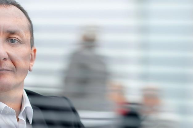 Fechar-se. homem de negócios sério em frente a janela do escritório. pessoas de negócio