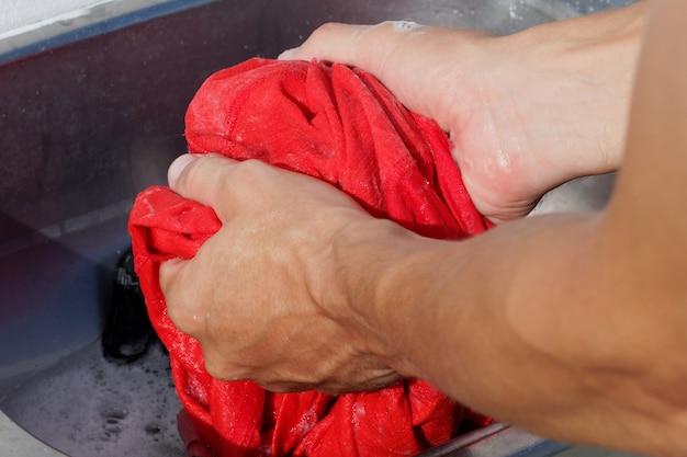 Fechar-se. homem lava roupas esportivas na pia.