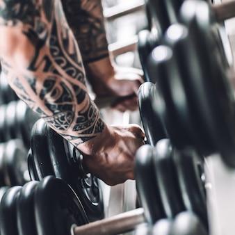 Fechar-se. homem musculoso levantando um haltere da prateleira