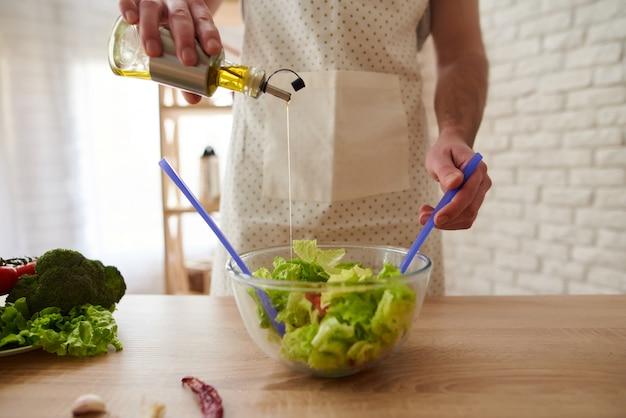 Fechar-se. homem no avental derrama azeite em salada.