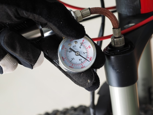 Fechar-se. homem que serve uma bicicleta, verificando uma pressão de ar no absorvedor pneumático.
