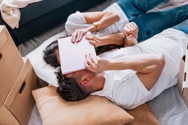 Fechar-se. jovem casal descansando no chão, no dia da mudança para um novo apartamento.