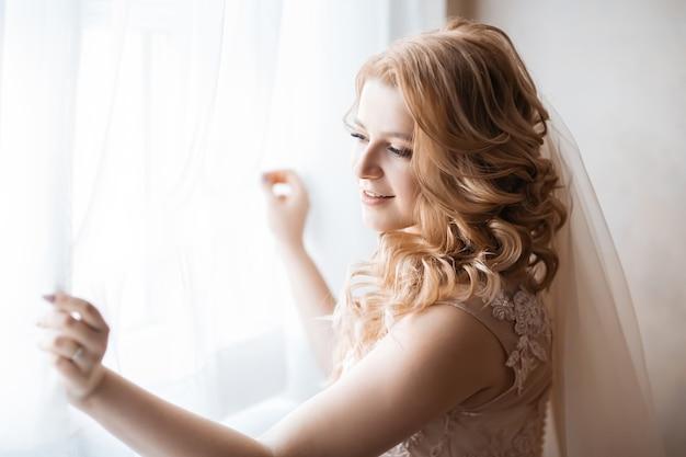 Fechar-se. jovem mulher vestida de noiva em pé perto da janela. feriados e eventos