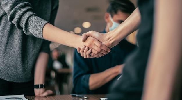 Fechar-se. jovens apertando as mãos no escritório.