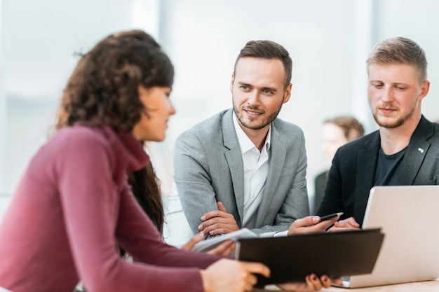 Fechar-se. jovens funcionários discutindo problemas em uma reunião de grupo.