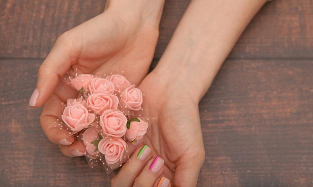 Fechar-se. lindas mãos femininas com manicure moderna e flores cor de rosa