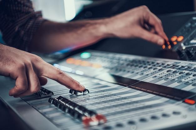 Fechar-se. macho mãos ajustando o controlador de áudio.