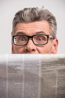 Fechar-se. macho sênior nos vidros que lê um jornal.