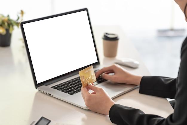 Fechar-se. mão de mulher de negócios segurando compras on-line de cartão de crédito usando uma tela branca em branco de laptop no escritório.