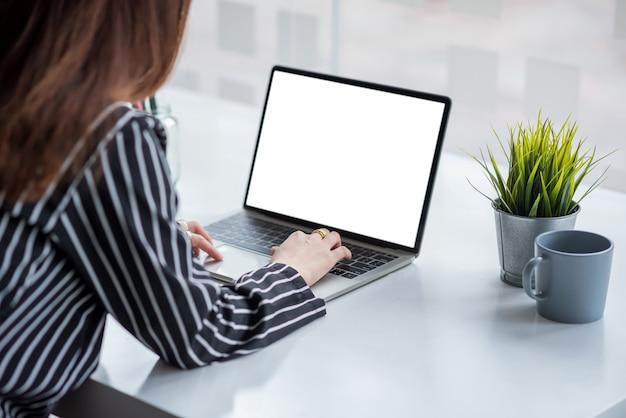 Fechar-se. mão de mulher de negócios usando laptop em tela branca na mesa