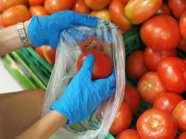 Fechar-se. mãos femininas em luvas azuis, escolhendo um tomate no supermercado durante o coronavírus pandêmico covid-19.