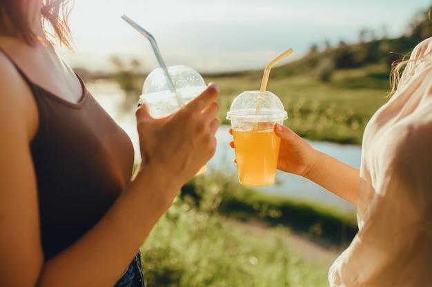 Fechar-se. meninas com dois copos de plástico com suco de laranja, com palha, ao pôr do sol, expressão facial positiva, ao ar livre
