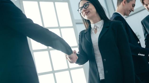 Fechar-se. mulher de negócios jovem apertando as mãos de seu parceiro de negócios. conceito de negócios.