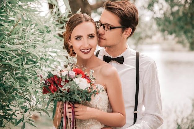 Fechar-se. noivo feliz beijando a noiva no parque da cidade