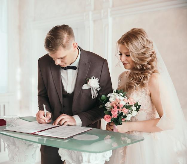 Fechar-se. o casal feliz ao assinar um contrato de casamento. feriados e eventos