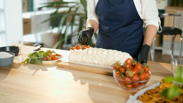 Fechar-se. o chef de confeitaria coloca morangos frescos em um bolo de merengue com creme.