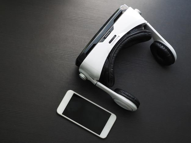 Fechar-se. óculos de realidade virtual e smartphone na mesa, tiro do estúdio. vista do topo.