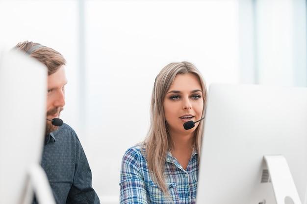 Fechar-se. operador feminino no fone de ouvido no local de trabalho. foto com espaço para texto