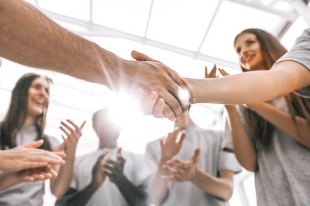 Fechar-se. os delegados da reunião de jovens, apertando as mãos uns dos outros. negócios e educação