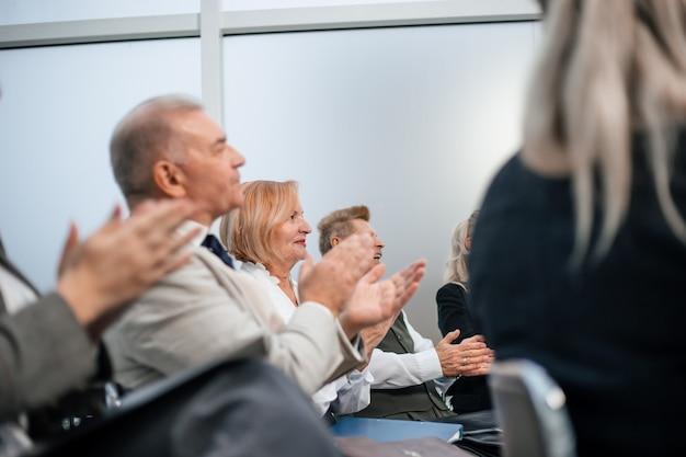 Fechar-se. os participantes do seminário aplaudem na sala de conferências. negócios e educação