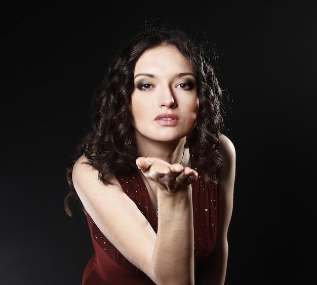 Fechar-se. retrato de uma linda mulher vestida de vermelho mandando um beijo.
