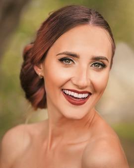 Fechar-se. retrato de uma linda noiva no fundo da folhagem de primavera