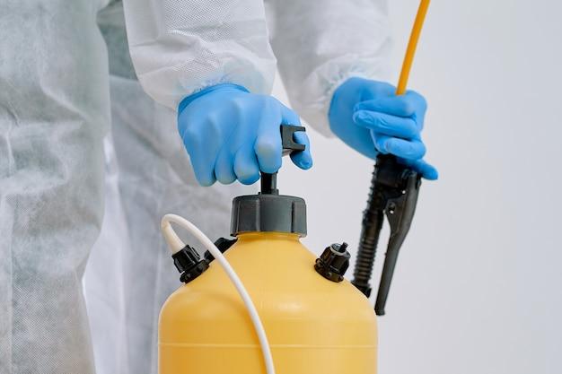 Fechar-se. trabalhador do serviço de descontaminação usando um recipiente com desinfetante.