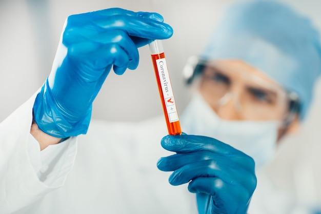 Fechar-se. tubo de ensaio nas mãos de um assistente de laboratório. ciência e saúde.