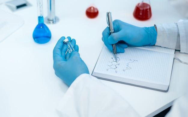 Fechar-se. um cientista escrevendo a fórmula de um novo medicamento. foto com uma cópia-espaço.