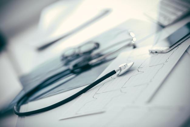 Fechar-se. um estetoscópio e um smartphone na mesa do terapeuta. foto com espaço de cópia