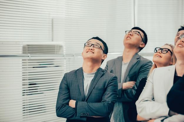 Fechar-se. um grupo de jovens empresários olhando para cima. foto com cópia-espaço