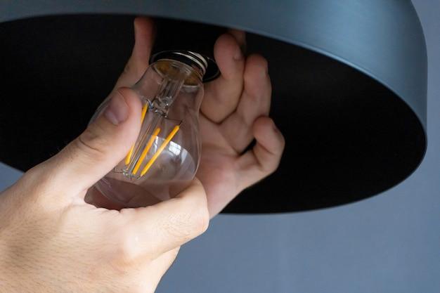 Fechar-se. uma mão muda uma lâmpada em uma lâmpada de loft elegante. lâmpada de filamento em espiral. decoração de interiores moderna.