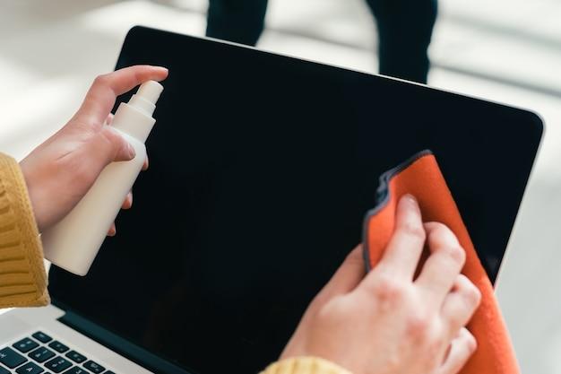 Fechar-se. uma mulher limpando a tela do laptop com um guardanapo anti-séptico.