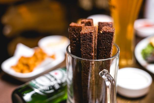 Fechar vista frontal cerveja lanche croutons de pão integral em um copo
