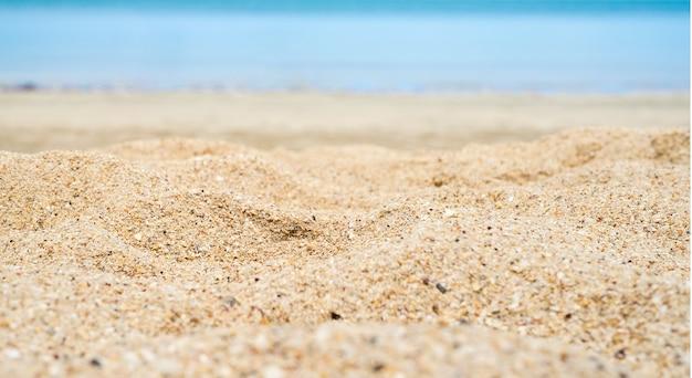 Feche a areia da praia com o mar ao fundo.