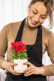 Feche a bela jardineira segura o vaso de cerâmica com petúnias florescendo nas mãos, foco em flores, florista jovem feliz cultivando flores, horta doméstica, hobby de jardinagem, floricultura