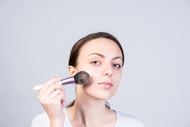 Feche a bela jovem aplicando maquiagem foundation no rosto usando um pincel, enquanto olha para a câmera, isolada em um fundo cinza.