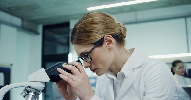 Feche a bela jovem caucasiana em copos trabalhando no laboratório e olhando no microscópio e, em seguida, digitando no computador portátil. câmera com menos zoom.
