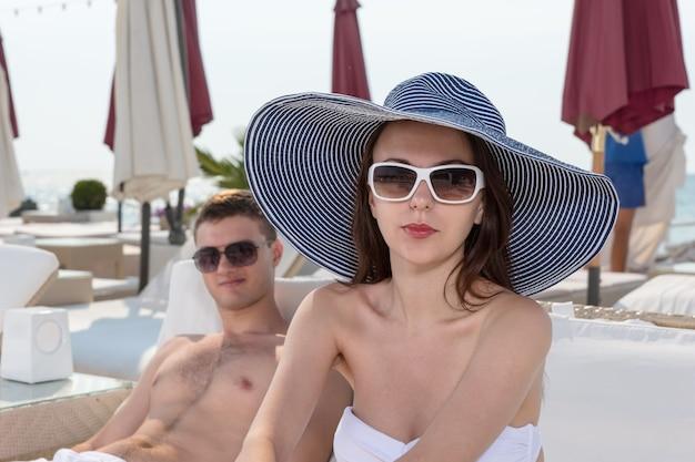 Feche a bela jovem em moda verão praia, olhando para a câmera enquanto está sentado na espreguiçadeira com o namorado ao lado dela.