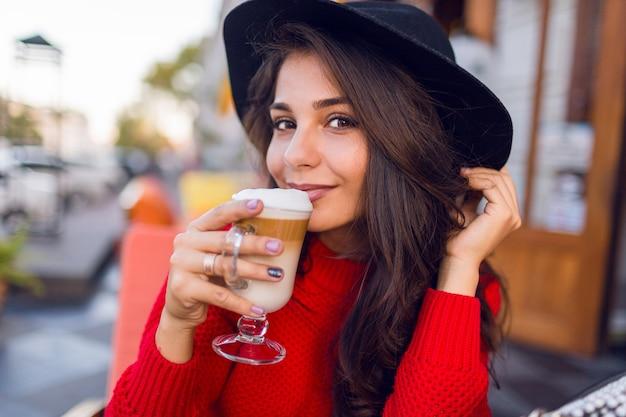 Feche a bela jovem morena de chapéu preto elegante e blusa vermelha brilhante, sentado no café de espaço aberto e beba café com leite ou cappuccino na manhã ensolarada.