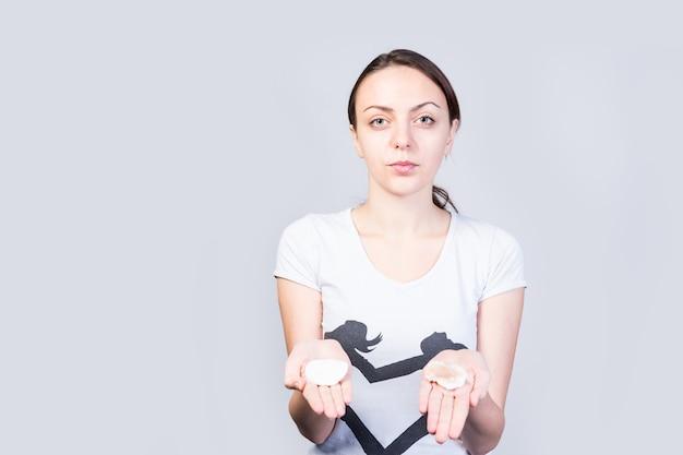 Feche a bela jovem mostrando algodões limpos e sujos nas palmas das mãos, enquanto olha para a câmera contra um fundo branco.