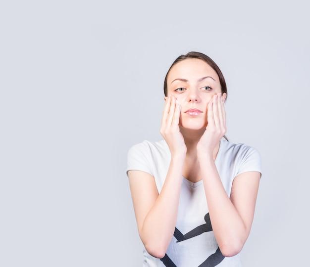 Feche a bela jovem tocando suas bochechas com as duas mãos enquanto olha para longe a sério, contra um fundo branco com espaço de cópia.