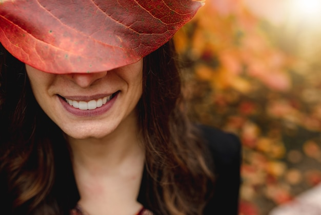 Feche a boca sorridente jovem cobrindo os olhos com uma folha vermelha. temporada outono, conceito de cor vermelha.