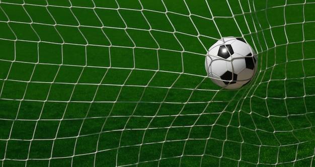 Feche a bola de futebol de futebol preto e branco marcando na rede do gol sobre a grama verde do campo de futebol com linhas de marcação brancas, ângulo alto, visão traseira da rede