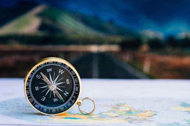 Feche a bússola no mapa de papel, viagens e estilo de vida, gerencie para o conceito de tecnologia de negócios de sucesso.